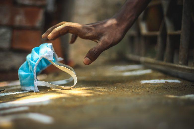 Pessoa pobre pegando uma máscara de proteção azul em meio a tijolos