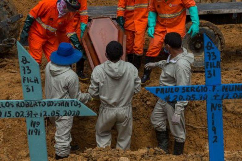 Coveiros dentro de uma cova colocando o caixão